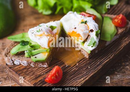 Oeuf poché, snack-avocat sandwich grillé sur planche à découper en bois. Vue rapprochée, selective focus Banque D'Images