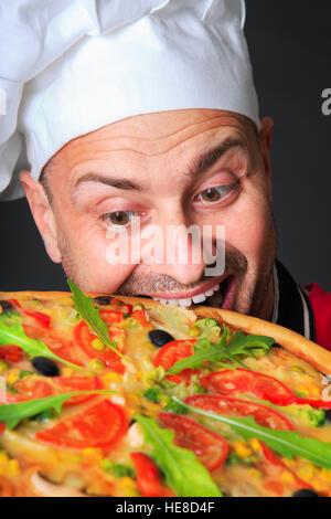 Portrait of happy cook attrayant avec une pizza en studio un fond noir Banque D'Images