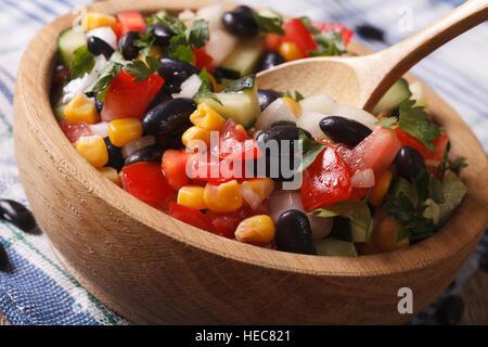 Salade de légumes mexicains avec les haricots noirs, d'avocat et de maïs close up dans une plaque de bois horizontal. Banque D'Images