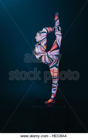 Jeune blonde souple circus acrobat posing in studio en costume. Faire l'équilibre equilibre headphones un cube. Banque D'Images