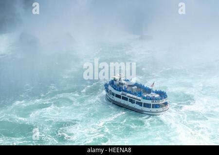 La femme de chambre dans la brume voile croisières à la pulvérisation de Niagara Falls. Banque D'Images
