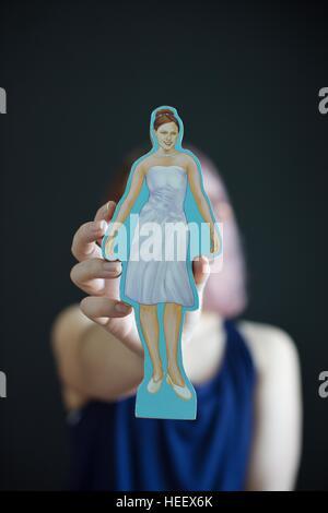 Une jeune fille tenant une découpe représentation d'une femme qui répond aux attentes de la société de la féminité. Banque D'Images