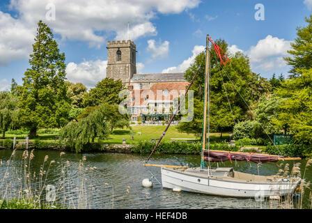 Bateau à voile sur la rivière Frome près de Wareham avec la dame de l'église St.Mary en arrière-plan, Dorset, Angleterre Banque D'Images