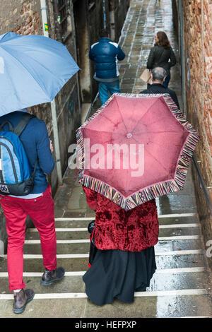 Personnes porteuses de parapluies dans une ruelle sous la pluie, Castello, Venise, Vénétie, Italie Banque D'Images