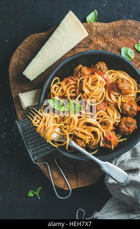 Dîner de pâtes italiennes. Spaghetti avec meatballas, basilic et parmesan en plaque noire sur fond de bois rustique Banque D'Images