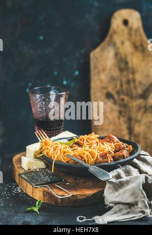 Dîner de pâtes italiennes. Spaghetti avec meatballas, basilic et parmesan dans la plaque noire et le vin rouge dans Banque D'Images