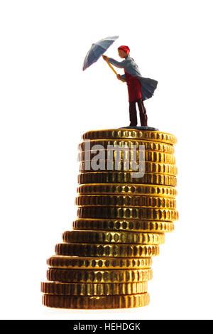 Femme debout Miniature sur une pile de pièces, l'ouverture d'un parapluie Banque D'Images