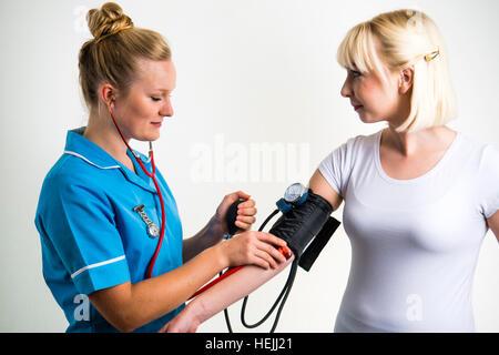 Les professionnels de la Santé du Royaume-Uni: A National Health Service (NHS) femme infirmière prenant une pression Banque D'Images