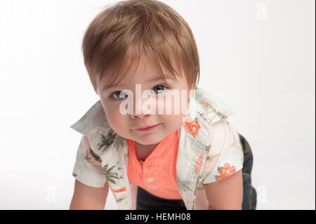 Un curieux dix mois, bébé garçon à la recherche dans l'appareil. Il est l'exploration sur un fond transparent, blanc. Banque D'Images