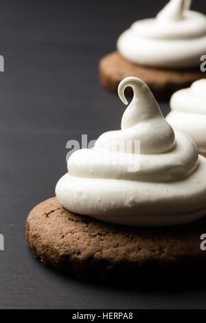 Les cookies au chocolat chaud avec de la guimauve meringue sur fond noir Banque D'Images