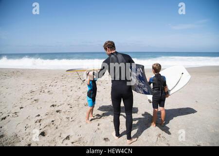 Vue arrière du père et ses deux fils se préparer à aller le bodyboard sur beach, Laguna Beach, Californie, USA Banque D'Images