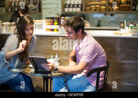 Young couple in cafe looking at digital tablet Banque D'Images
