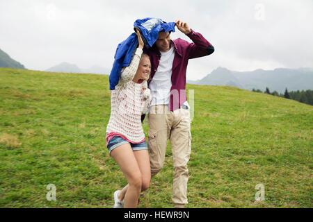 Jeune couple running down hill holding up anorak dans la pluie, Sattelbergalm, Tyrol, Autriche Banque D'Images