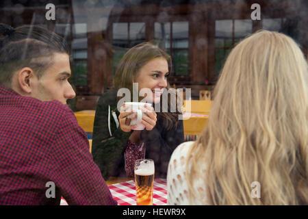 Trois jeunes amis adultes avec thé et café dans la bière Banque D'Images