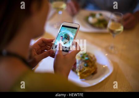 Woman taking photograph de sa nourriture sur la table Banque D'Images