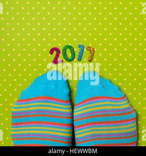 Capture d'un grand angle d'une paire de chaussettes à rayures colorées portant des pieds et quelques chiffres scintillants Banque D'Images