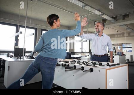 Deux collègues jouer au baby-foot et haute fiving in office Banque D'Images
