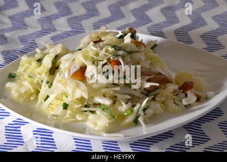 Avec salade de choux et les champignons sur une plaque blanche Banque D'Images