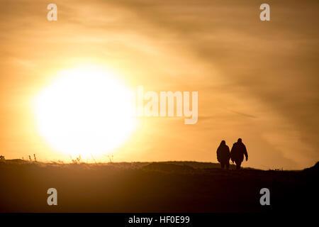 Un couple de promeneurs de chiens profiter du gel sur la montagne Halkyn, Flintshire au lever du soleil, marcher Banque D'Images