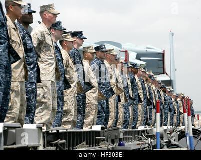 Marines avec la 22e unité expéditionnaire de Marines et marins avec un homme USS Bataan les rails comme Bataan navigue Banque D'Images