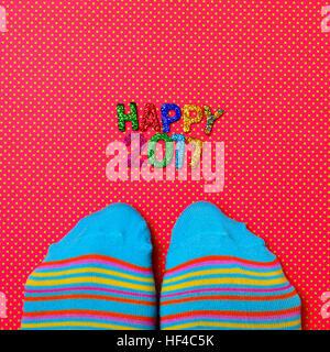 Capture d'un grand angle d'une paire de chaussettes à rayures colorées portant des pieds et quelques lettres brillantes Banque D'Images