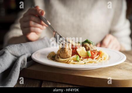 Woman eating spaghetti aux boulettes de l'horizontale Banque D'Images