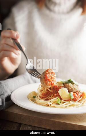 Femme mangeant des boulettes de vertical plat Banque D'Images