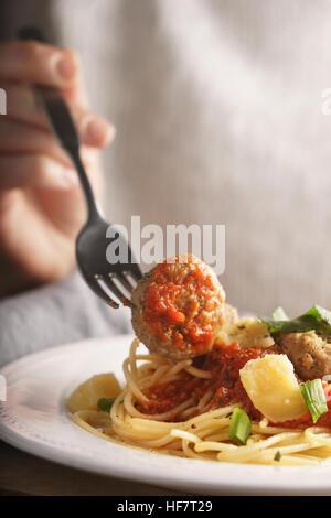Woman eating spaghetti aux boulettes de viande à la verticale Banque D'Images