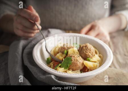 Woman eating spaghetti aux boulettes de viande à partir d'une horizontale bol Banque D'Images