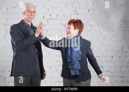 Donner une haute de cinq ans. Happy smiling old woman cuddling ensemble isolé sur fond de brique blanche. copier l'espace.