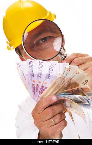 Construction Worker wearing hardhat jaune tenant une loupe sur les espèces en euros Banque D'Images