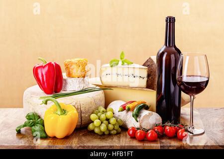 De nombreux types de fromages français - rondin de brebis ossau-iraty,, camembert, comte, vieux, tomme de chèvre, Langres, morbier, margalet avec bouteille de vin