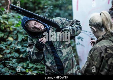 Des groupes de gens habillés en tenue de camouflage combat et transportant des armes de paint-ball zombies de chasse Banque D'Images