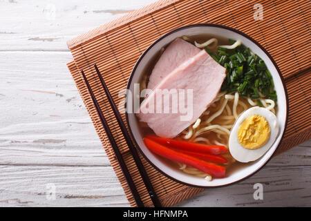 La nourriture asiatique: nouilles ramen dans un bouillon avec du porc, des légumes et d'oeuf dans un bol de près. Banque D'Images