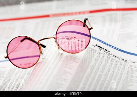 Des lunettes roses sur le dessus d'un journal financier