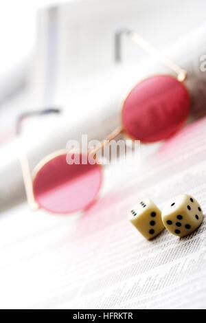 Des lunettes roses et les dés sur le dessus d'un journal financier