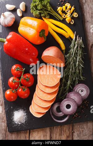 Ingrédients: légumes patates douces, poivrons, tomates, oignons, ail, romarin et d'épices sur une liste de sélection. Banque D'Images