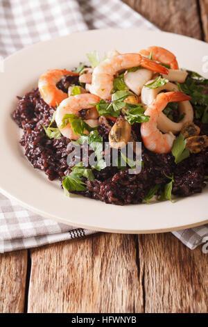 Riz Noir avec les crevettes, les calmars, les moules et les pétoncles sur le gros plan de la plaque verticale. Banque D'Images