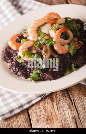 Riz noir sauvage avec les crevettes, les calmars, les moules et les pétoncles close up sur une plaque verticale Banque D'Images
