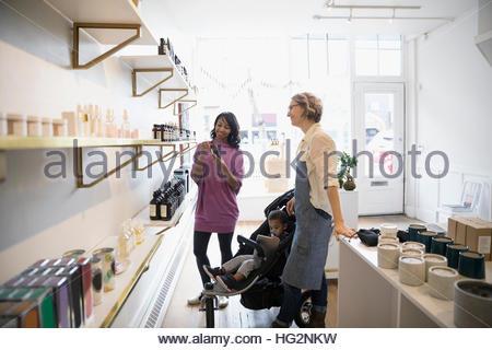 Femme propriétaire de boutique d'aider la mère et le fils avec home fragrances dans shop Banque D'Images