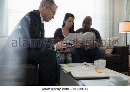 Conseiller financier avec la calculatrice rencontre avec couple in living room Banque D'Images