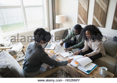 Conseiller financier discussing paperwork with couple in living room Banque D'Images