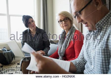 Conseiller financier avec ordinateur portable et paperasse rencontre avec couple dans la salle de séjour Banque D'Images
