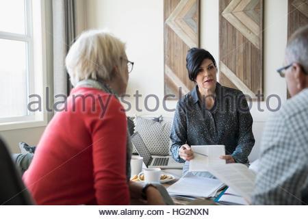 Conseiller financier expliquant la paperasse rencontre avec couple dans la salle de séjour Banque D'Images