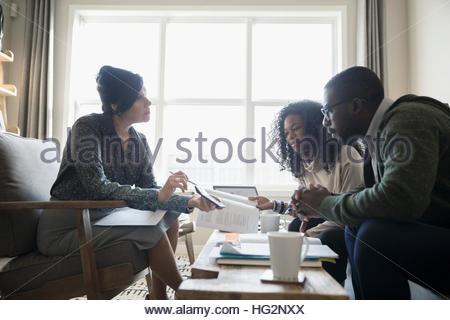 Conseiller financier montrant calculatrice pour rencontre couple dans la salle de séjour Banque D'Images