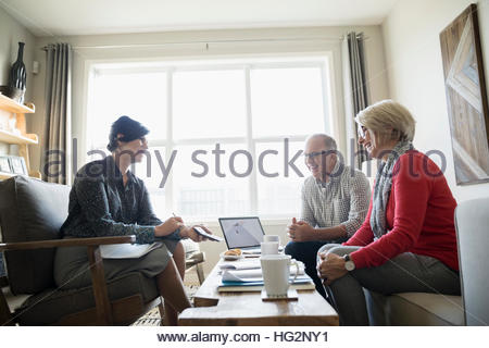 Conseiller financier montrant calculatrice pour senior couple séance dans la salle de séjour Banque D'Images