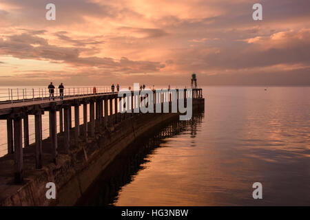Au coucher du soleil, les gens et pier sont découpé sur le spectaculaire, ciel et mer rouge vif - Whitby, North Banque D'Images