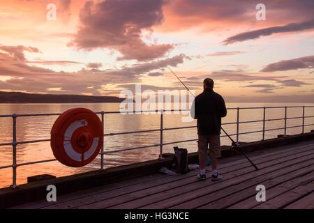 Scenic Whitby & silhouetté contre dramatique, bright colorful sunset sky, man (pêcheur) est la pêche en mer à partir Banque D'Images