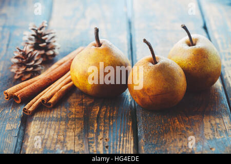 Poires biologiques avec des bâtons de cannelle sur une table en bois Banque D'Images