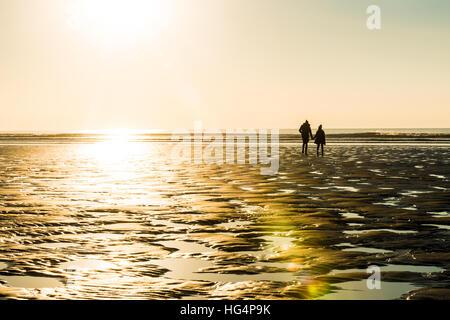 Un couple en train de marcher sur la plage le soir Banque D'Images